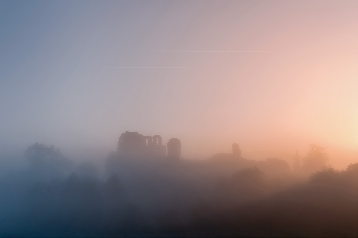 ​Fog swirls around the ruined remains of Clun Castle in Shropshire as the cold of the night makes way for the warmth of the Autumn day.