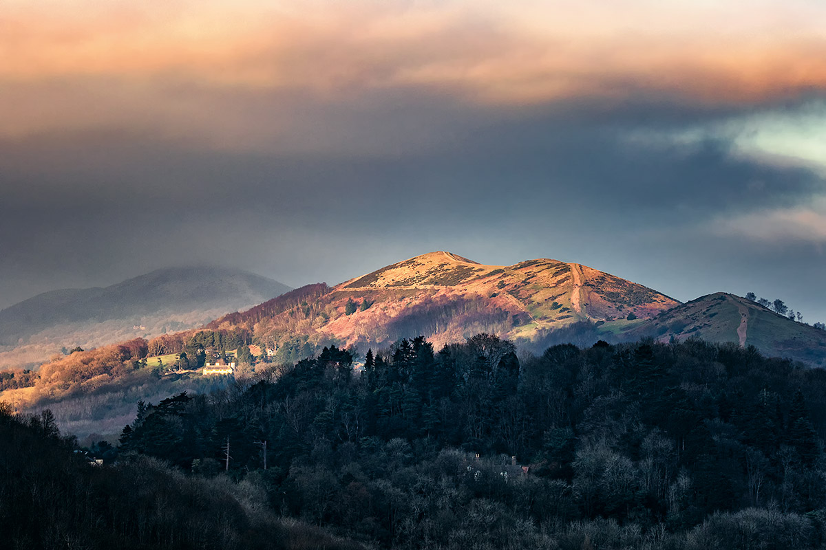 A fleeting moment of sunlight glancing off the flanks of the Malvern Hills in Worcestershire